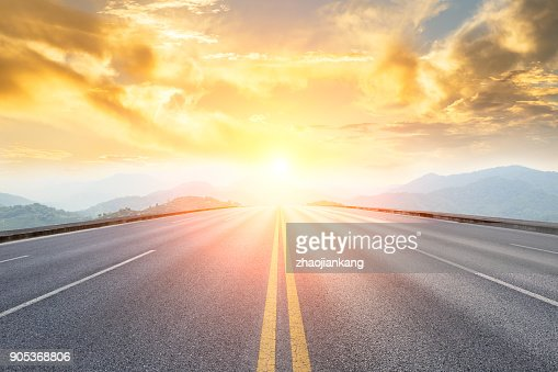 asphalt road and mountains with foggy landscape at sunset : Stock Photo