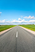 Asphalt Road in fields with white car standing on wayside. Colorful summertime outdoors vertical image with perspective.