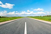 Asphalt road in green fields on blue cloudy sky background. Multicolored vibrant outdoors horizontal image.