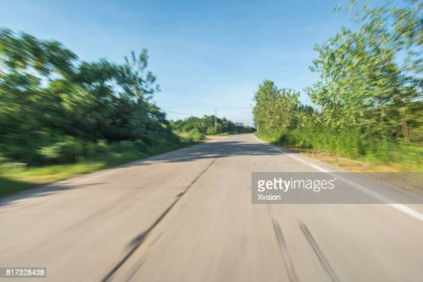 Asphalt road under blue sky with clouds in motion blur with plants in sides