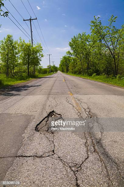 Asphalt road with pothole in the countryside, Quebec, Canada