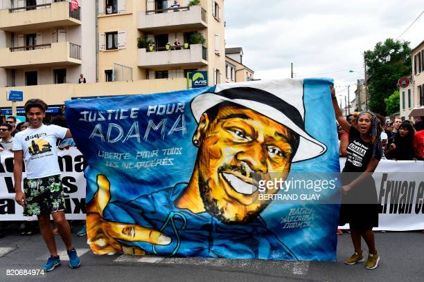 Assa Traore the elder sister of late Adama Traore who died during his arrest by the police in July 2016 holds a banner reading 'Justice for Adama...