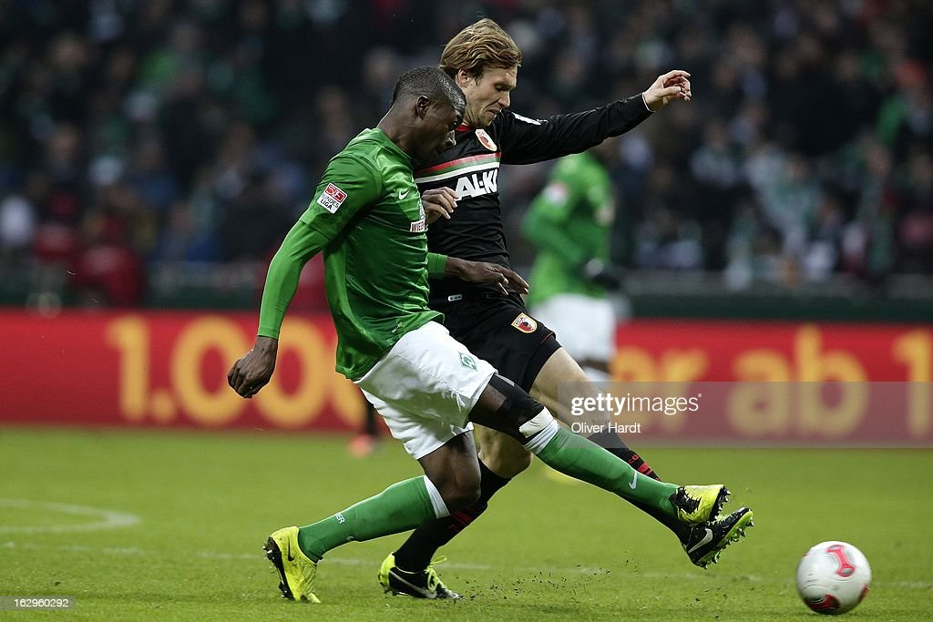 Assani Lukimya (L) of Bremen and <a gi-track='captionPersonalityLinkClicked' href=/galleries/search?phrase=Andreas+Ottl&family=editorial&specificpeople=645670 ng-click='$event.stopPropagation()'>Andreas Ottl</a> (R) of Augsburg battle for the ball during the Bundesliga match between SV Werder Bremen and FC Augsburg at Weser Stadium on March 2, 2013 in Bremen, Germany.