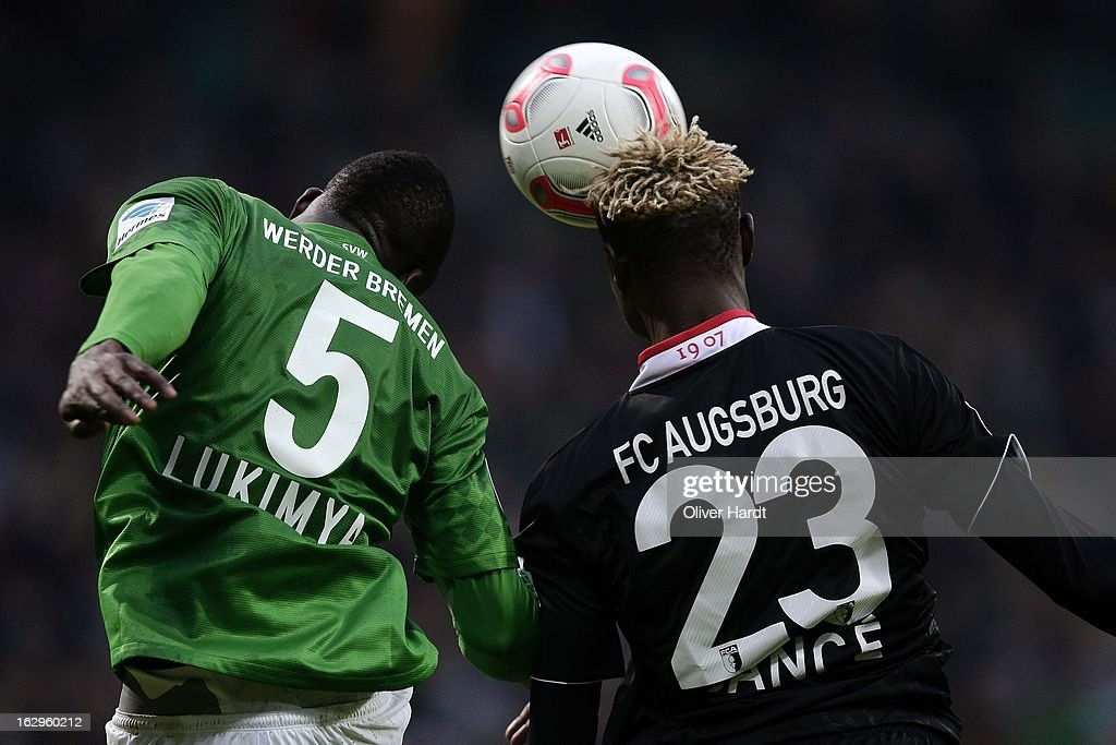 Assani Lukimya (L) of Bremen and Aristide Bance (R) of Augsburg battle for the ball during the Bundesliga match between SV Werder Bremen and FC Augsburg at Weser Stadium on March 2, 2013 in Bremen, Germany.