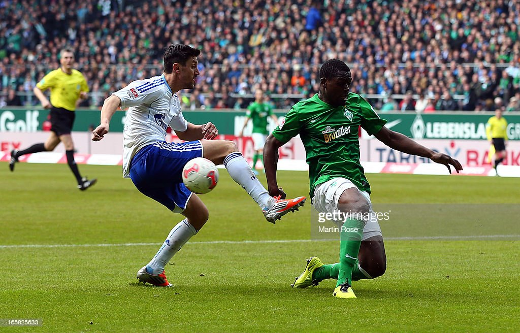 Assani Lukimya (R) of Bremen and <a gi-track='captionPersonalityLinkClicked' href=/galleries/search?phrase=Ciprian+Marica&family=editorial&specificpeople=2178476 ng-click='$event.stopPropagation()'>Ciprian Marica</a> (L) of Schalke battle for the ball during the Bundesliga match between Werder Bremen and FC Schalke 04 at Weser Stadium on April 6, 2013 in Bremen, Germany.