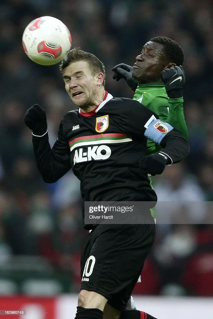 Assani Lukimya (R) of Bremen and Daniel Baier (R) of Augsburg battle for the ball during the Bundesliga match between SV Werder Bremen and FC Augsburg at Weser Stadium on March 2, 2013 in Bremen, Germany.