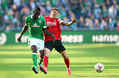 Assani Lukimya of Bremen and Mike Frantz of Freiburg battle for the ball during the Bundesliga match between SV Werder Bremen and SC Freiburg at...