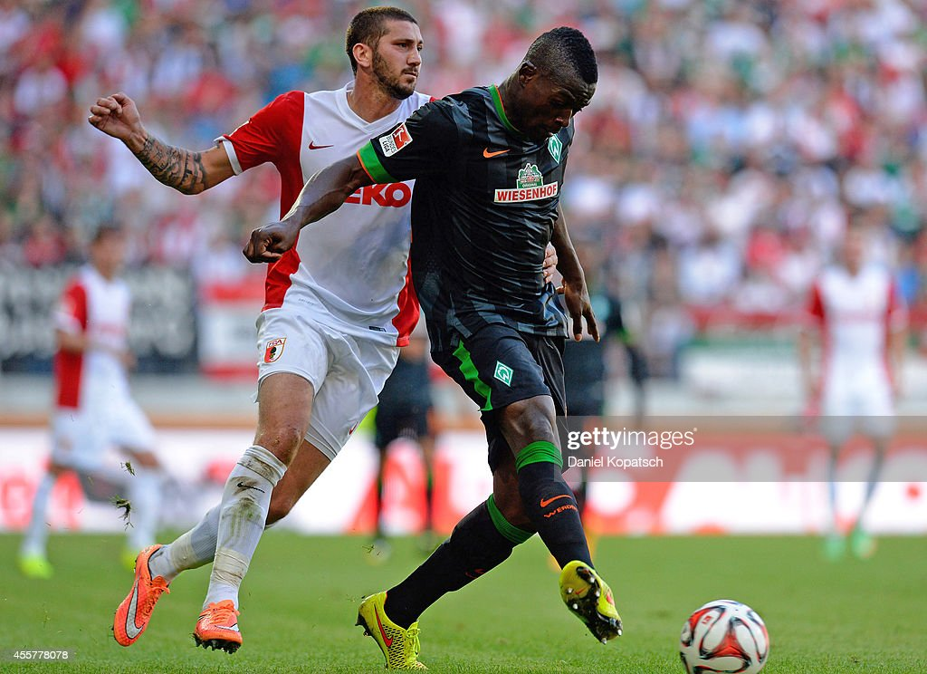 Assani Lukimya of Bremen is challenged by Sascha Moelders of Augsburg during the Bundesliga match between FC Augsburg and SV Werder Bremen at SGL...