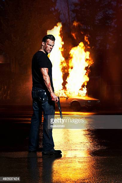 Assassin Standing in Front of a Blown Up Car