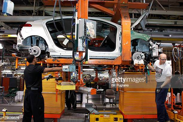 Assembly line workers assemble Chevy Volt electric vehicles and Opel Amperas at the General Motors Detroit Hamtramck Assembly Plant October 11 2011...