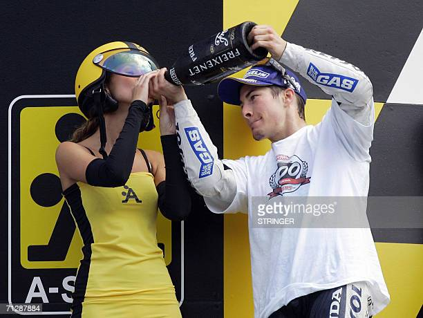 US rider Nicky Hayden shares his champagne with a model after winning the Dutch MotoGP in Assen 24 June 2006 AFP PHOTO / ANP VINCENT JANNINK