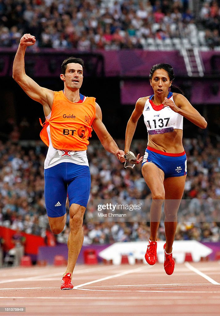 <a gi-track='captionPersonalityLinkClicked' href=/galleries/search?phrase=Assia+El+Hannouni&family=editorial&specificpeople=2905697 ng-click='$event.stopPropagation()'>Assia El Hannouni</a> of France and her guide Gautier Simounet cross the line to win gold in the Women's 200m - T12 on day 8 of the London 2012 Paralympic Games at Olympic Stadium on September 6, 2012 in London, England.