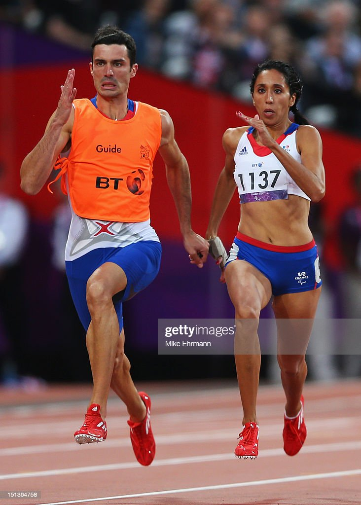 <a gi-track='captionPersonalityLinkClicked' href=/galleries/search?phrase=Assia+El+Hannouni&family=editorial&specificpeople=2905697 ng-click='$event.stopPropagation()'>Assia El Hannouni</a> of France and her guide Gautier Simounet on their way to winning gold in the Women's 200m - T12 on day 8 of the London 2012 Paralympic Games at Olympic Stadium on September 6, 2012 in London, England.
