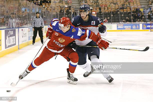 Assistant Captain Danila Kvartalnov of Team Russia fights off Patrik Osko of Team Slovakia in the attacking zone during the 1st period in a...