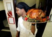 Assistant Chef Joe Breaton carries out a turkey prior to actor Stephen Baldwin serving Thanksgiving dinner to men and women at the New York City...