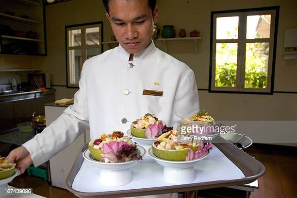 Assistant chef Sudjarit gathers dishes prepared by students at the Thai Cooking School at the Oriental Hotel