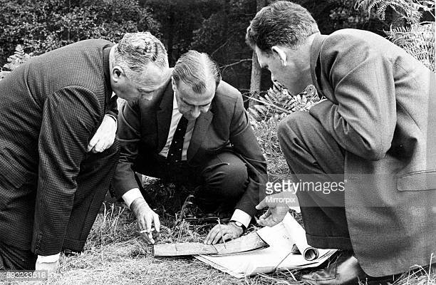 Assistant Chief Constable S E Bailey Det Chief Supt H Bailey and Det Insp Fernihough study aerial pictures with a stereoscopic viewer amongst the...