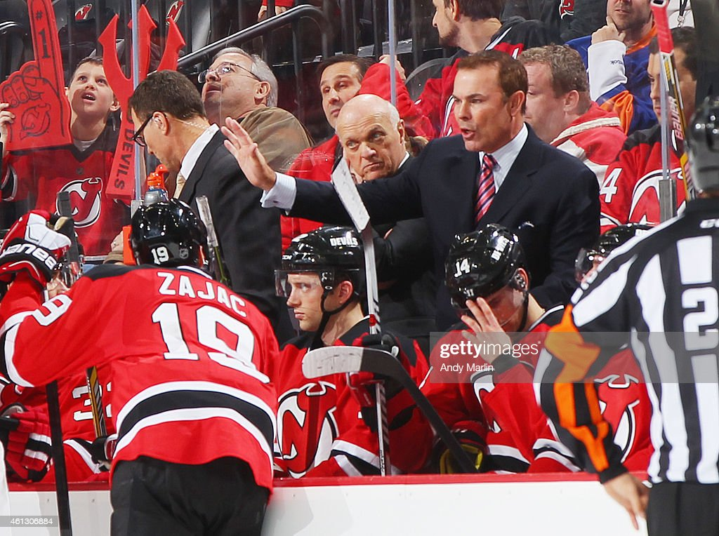 Assistant coach Adam Oates of the New Jersey Devils gives instructions during a timeout during the game against the New York Islanders at the...