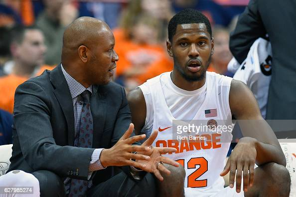 Assistant coach Adrian Autry of the Syracuse Orange talks with Taurean Thompson on the bench against the North Florida Ospreys during the second half...