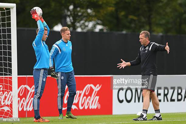Assistant coach Andreas Koepcke talks to his players MarcAndre ter Stegen and Bernd Leno during a training session of the German national football...