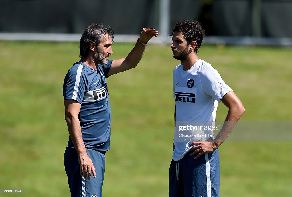Assistant coach Angelo Gregucci (L) and Andrea Ranocchia chat during a FC Internazionale training session on August 7, 2016 in Milan, Italy.