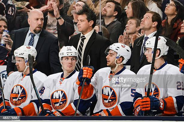 Assistant Coach Brent Thompson left Head Coach Jack Capuano center and Assistant Coach Doug Weight right all of the New York Islanders watch their...