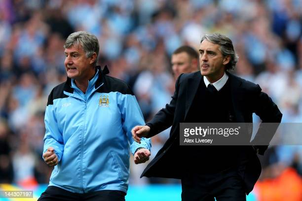 Assistant coach Brian Kidd and Roberto Mancini the manager of Manchester City react during the Barclays Premier League match between Manchester City...