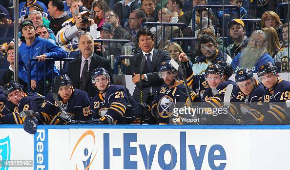 Assistant coach Bryan Trottier and head coach Ted Nolan and players of the Buffalo Sabres watch the action against the Boston Bruins on October 30...