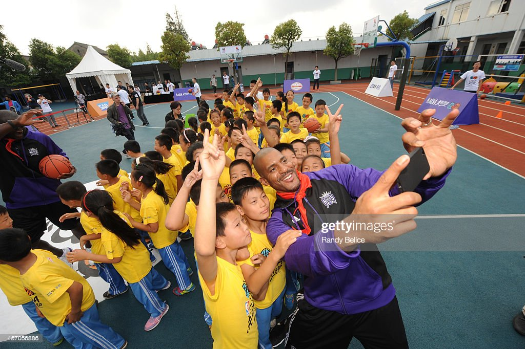 Assistant Coach Corliss Williamson of the Sacramento Kings takes a photo with the kids during the 2014 NBA Global Games NBA Cares Learn and Play...