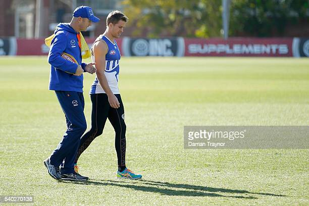 Assistant coach Darren Crocker speaks with Andrew Swallow during a North Melbourne Kangaroos AFL training session at Arden Street Ground on June 15...