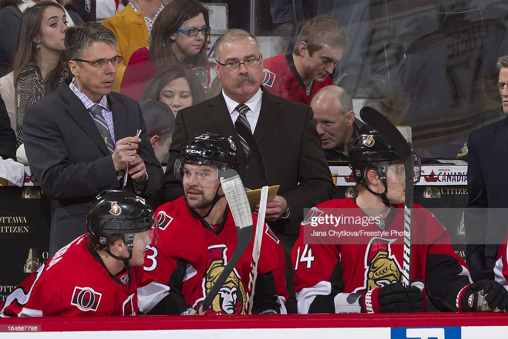 Assistant coach Dave Cameron (L) and head coach Paul MacLean (M) of the Ottawa Senators look on from the bench, during an NHL game against the Boston Bruins, at Scotiabank Place, on March 21, 2013 in Ottawa, Ontario, Canada.