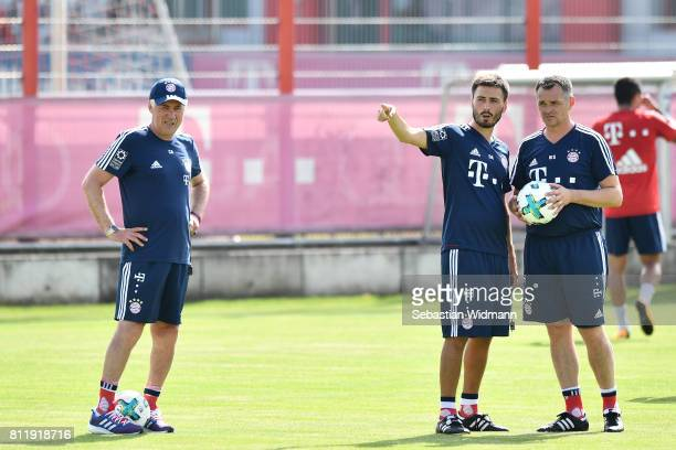 Assistant coach Davide Ancelotti and assistant coach Willy Sagnol talk while head coach Carlo Ancelotti stands next to them during a training session...