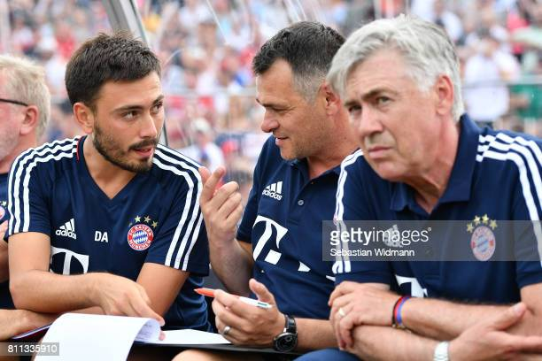 Assistant coach Davide Ancelotti and assistant coach Willy Sagnol talk to each other while head coach Carlo Ancelotti looks on during the preseason...