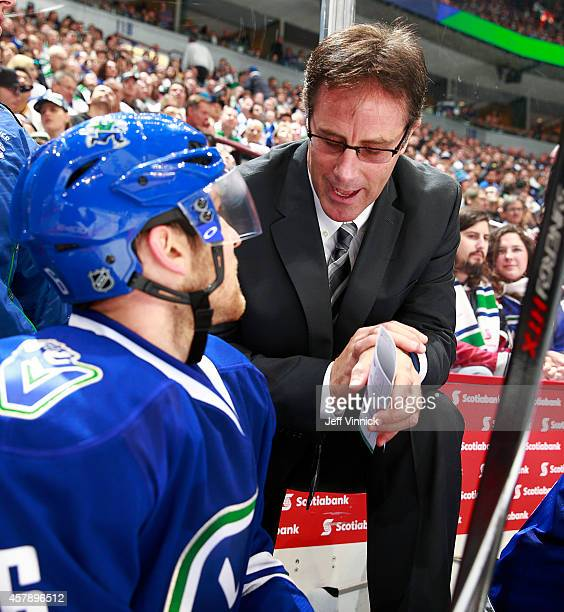 Assistant coach Doug Lidster of the Vancouver Canucks talks to Yannick Weber during their NHL game against theTampa Bay Lightning at Rogers Arena...