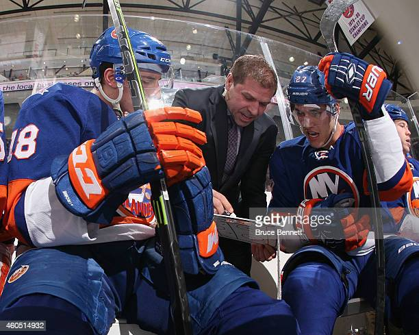 Assistant coach Doug Weight speaks with Ryan Strome and Anders Lee of the New York Islanders during the game against the New Jersey Devils at the...