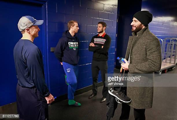 Assistant coach Glen Gulutzan and Jannik Hansen of the Vancouver Canucks talk with former teammates Kevin Bieksa and Ryan Kesler of the Anaheim Ducks...