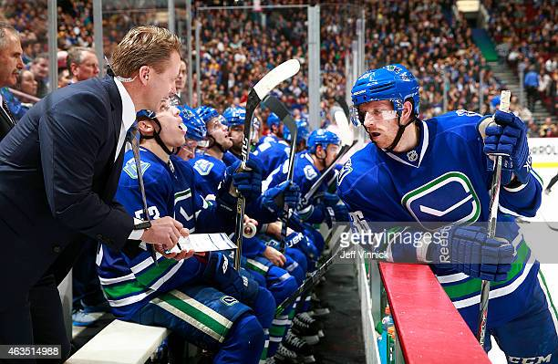 Assistant coach Glen Gulutzan of the Vancouver Canucks talks to Jannik Hansen of the Vancouver Canucks during their NHL game against the Boston...