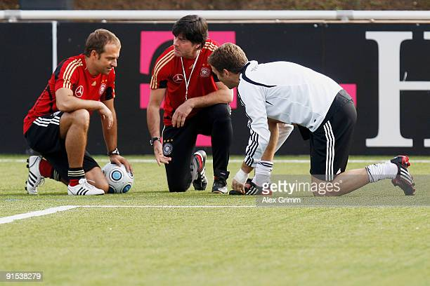 Assistant coach Hansi Flick head coach Joachim Loew and team manager Oliver Bierhoff check the artificial turf during a training session of the...