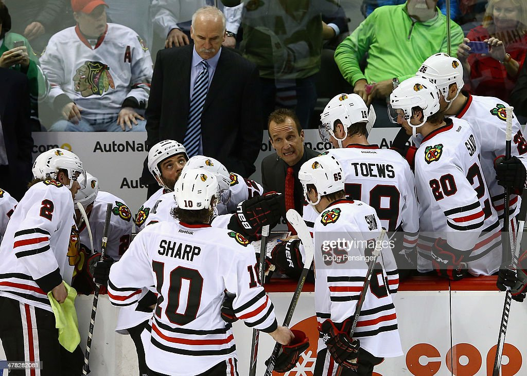 Assistant coach Jamie Kompon of the Chicago Blackhawks directs the team during a time out against the Colorado Avalanche as head coach <a gi-track='captionPersonalityLinkClicked' href=/galleries/search?phrase=Joel+Quenneville&family=editorial&specificpeople=2094832 ng-click='$event.stopPropagation()'>Joel Quenneville</a> looks on at Pepsi Center on March 12, 2014 in Denver, Colorado. The Avalanche defeated the Blackhawks 3-2.