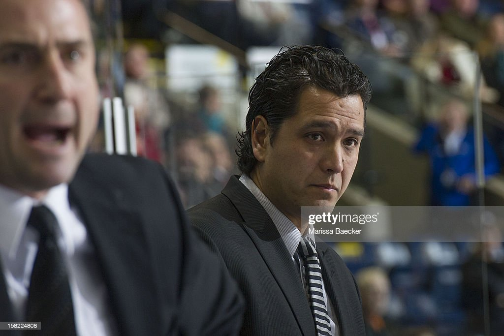 Assistant coach Jason Becker of the Prince George Cougars stands on the bench against the Kelowna Rockets on December 8, 2012 at Prospera Place in Kelowna, British Columbia, Canada.