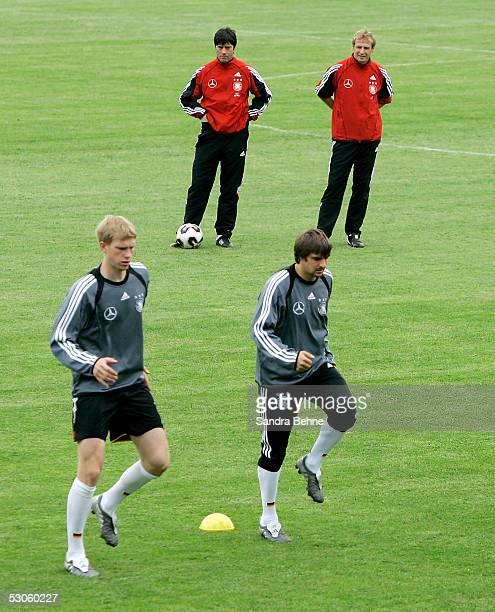 Assistant coach Joachim Loew and head coach Juergen Klinsmann watch over Per Mertesacker and Sebastian Deisler during the German National Team...