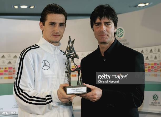 Assistant coach Joachim Low and Miroslav Klose hold the VDS Fair Play Trophy presented to Klose during the Press conference of the German National...