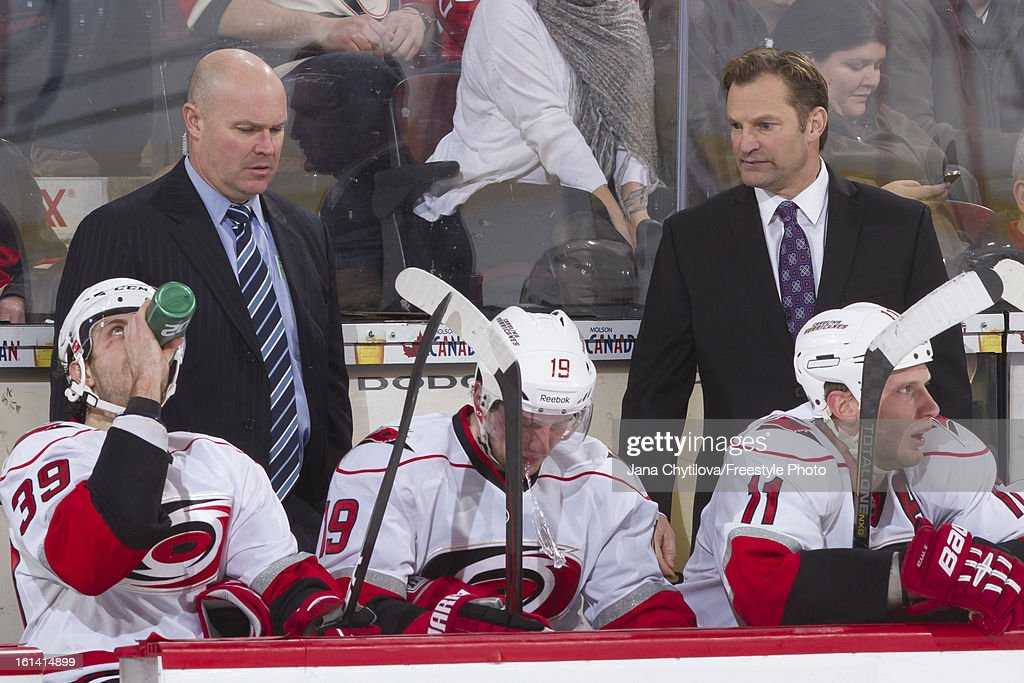 Assistant coach John MacLean (L) and head coach Kirk Muller (R) of the Carolina Hurricanes look on from the bench during an NHL game against the Ottawa Senators at Scotiabank Place on February 7, 2013 in Ottawa, Ontario, Canada.