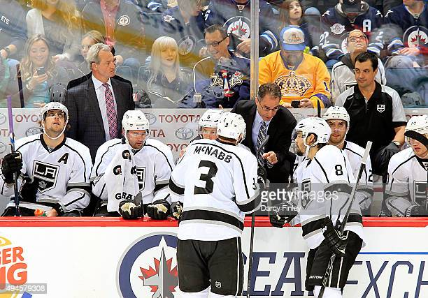 Assistant Coach John Stevens of the Los Angeles Kings instructs Brayden McNabb and Drew Doughty at the bench during a second period stoppage against...