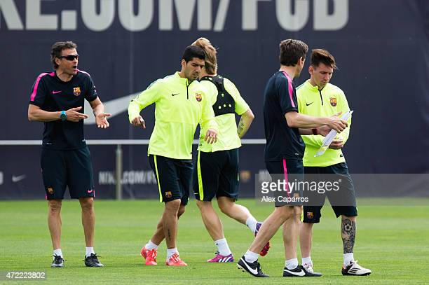 Assistant coach Juan Carlos Unzue of FC Barcelona gives instructions to Lionel Messi as head coach Luis Enrique Martinez speaks to Luis Suarez during...