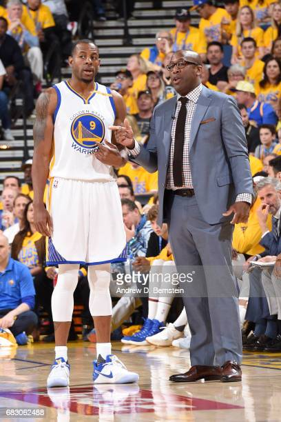 Assistant Coach Mike Brown and Andre Iguodala of the Golden State Warriors talk during the game against the San Antonio Spurs in Game One of the...