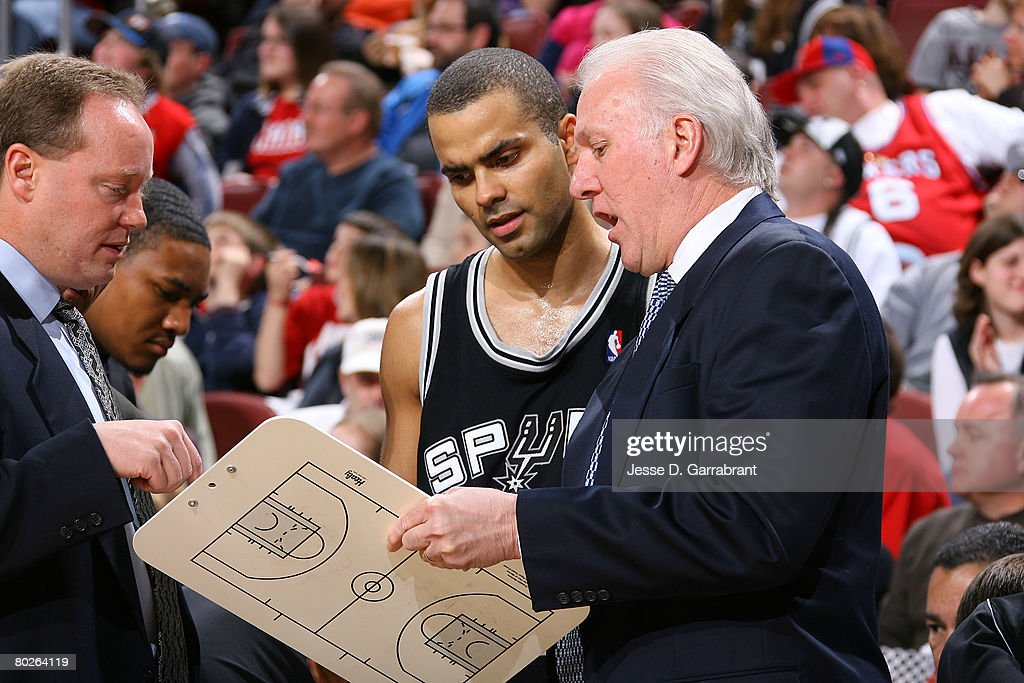 Assistant Coach, Mike Budenholzer; Tony Parker #9; and Head Coach, Gregg Popovich, of the San Antonio Spurs discuss a play during the game against the Philadelphia 76ers on March 15, 2008 at the Wachovia Center in Philadelphia, Pennsylvania.