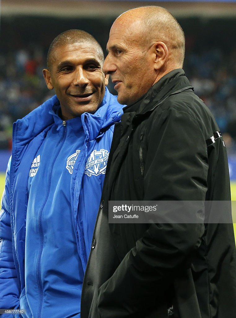 Assistant coach of OM Franck Passi talks to former coach of OM <a gi-track='captionPersonalityLinkClicked' href=/galleries/search?phrase=Elie+Baup&family=editorial&specificpeople=536928 ng-click='$event.stopPropagation()'>Elie Baup</a> before the French Ligue 1 match between Paris Saint-Germain FC and Olympique de Marseille OM at Parc des Princes stadium on November 9, 2014 in Paris, France.