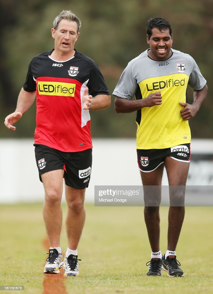 Assistant coach Paul Hudson runs with former Hawthorn player Carl Peterson during a St Kilda Saints AFL training session on November 8 2013 in...