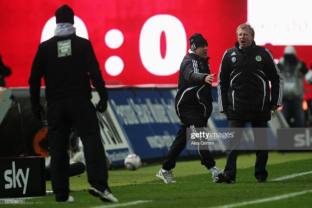 Assistant coach Pierre Littbarski of Wolfsburg stands between head coaches Steve McClaren of Wolfsburg and Marco Kurz of Kaiserslautern as they argue...